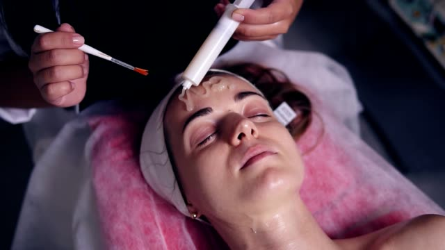 Carboxytherapy for young woman in professional spa salon. Young woman is lying on the couch while professional cosmetologist is apllying special treatment on woman's face using brush