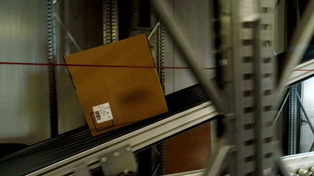 Cardboard boxes moving on a conveyor belt. Close up video