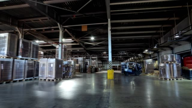 vídeos de stock e filmes b-roll de cardboard covered with foil in light warehouse timelapse - armazém