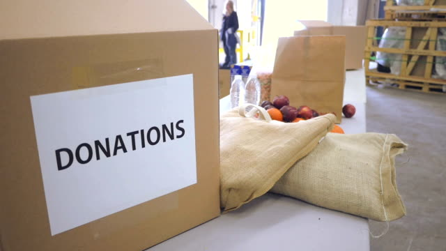 Cardboard donation boxes in food bank being filled with groceries video
