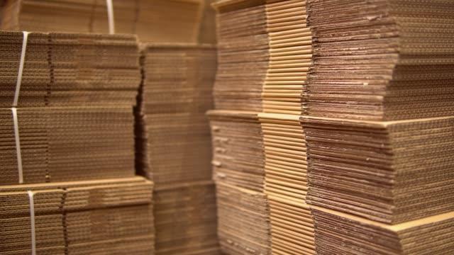 vídeos de stock e filmes b-roll de cardboard in warehouse - cardboard box