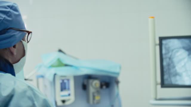 vídeos de stock, filmes e b-roll de cirurgião olhando monitor de frequência cardíaca - marcapasso cirurgia cardíaca