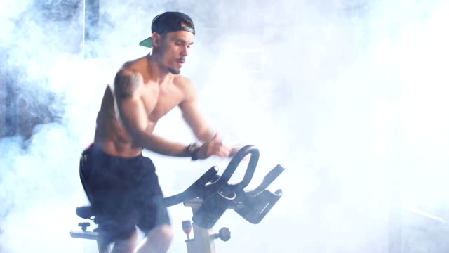 cardio workout. shirtless athletic man training on cycling machine in gym - man city exercise abs video stock e b–roll