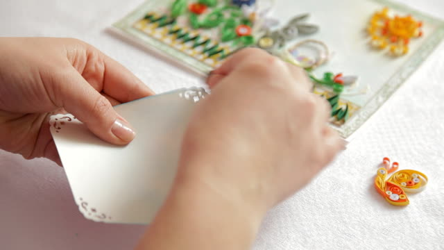 Cardmaking: unknown person is making greeting card indoors in process. video