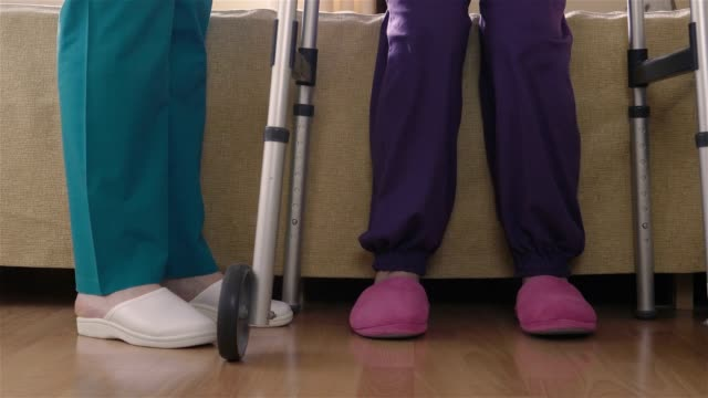 Care assistant teaching elder disabled woman how to walk with walker video