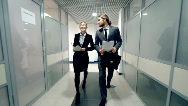 Career Path Workmates strolling along the office corridor discussing business office cubicle stock videos & royalty-free footage
