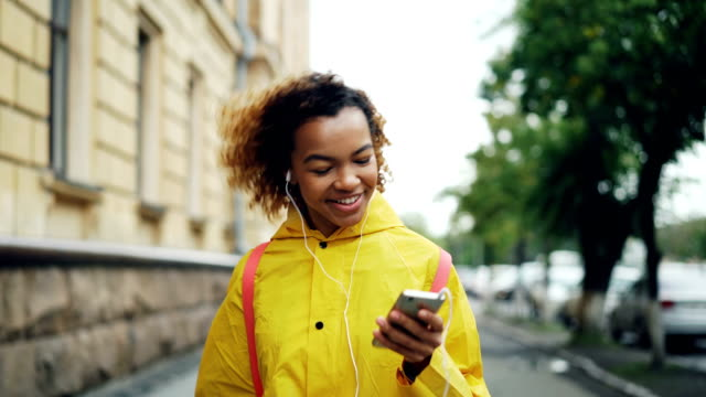 Carefree African American student is walking, listening to music through earphones and singing during leisure time. Modern technology, youth culture, cities and people concept.