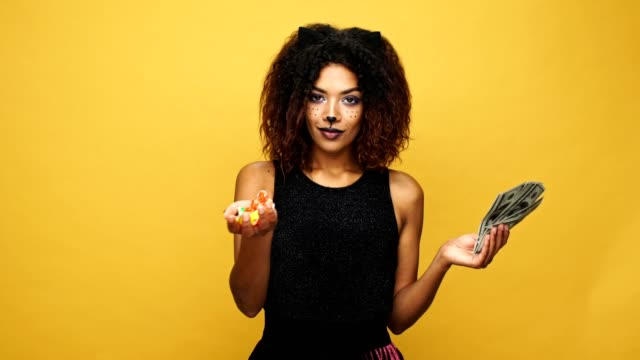 Carefree african lady with cat make up holding in hands candies and money, trick and treat isolated over yellow video