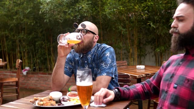 Carefree bearded men drinking beer and relaxing in a back yard