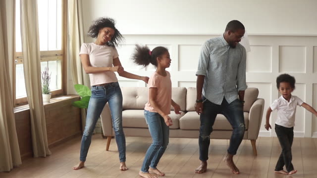 Carefree black parents and kids dancing together in living room