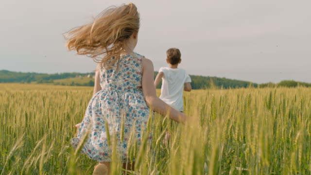 MS Carefree boy and girl running in sunny idyllic rural wheat field