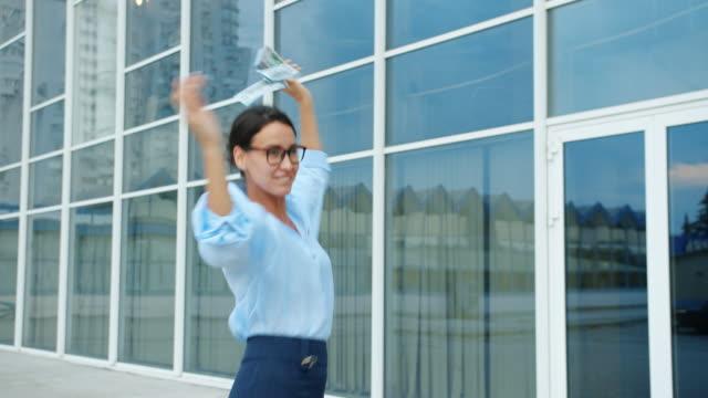 vídeos de stock e filmes b-roll de carefree businesswoman dancing outside office building throwing money having fun - enjoying wealthy life