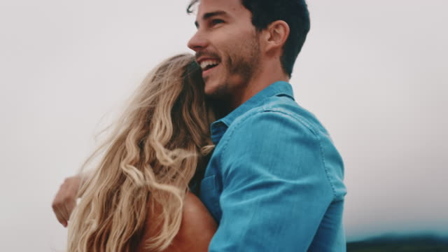Carefree couple dancing at beach during weekend Handheld shot of cheerful young couple embracing against sky. Carefree boyfriend is spinning girlfriend while dancing. They are enjoying weekend at beach. young couple stock videos & royalty-free footage