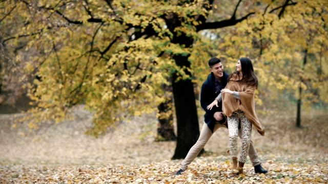 stockvideo's en b-roll-footage met zorgeloos paar plezier in herfstdag terwijl het achtervolgen in het forest. slow-motion. - s