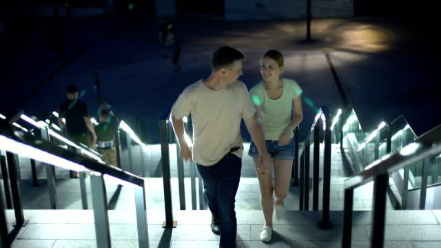 Carefree couple walking upstairs to embankment to watch illuminated night city