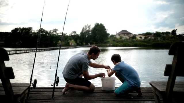 Carefree dad and son preparing to fish on the lake video