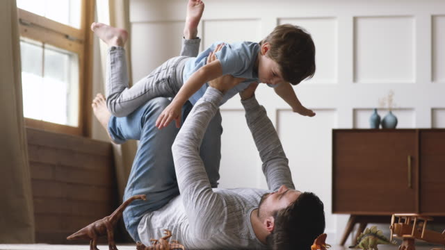 Carefree dad lifting little kid son pretend superhero playing together
