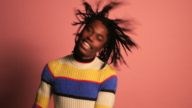 Carefree Dancing Portrait of a man dancing in front of a pink background, he is wearing a striped colourful jumper, he is enjoying himself and expressing his freedom. background color stock videos & royalty-free footage