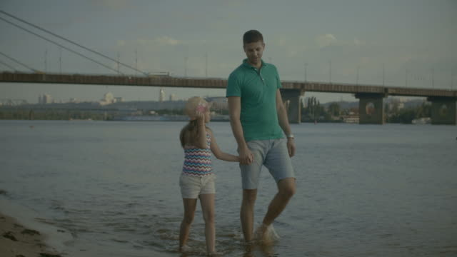 屈託のない父と娘は、ビーチの上を歩く - 川岸点の映像素材/bロール