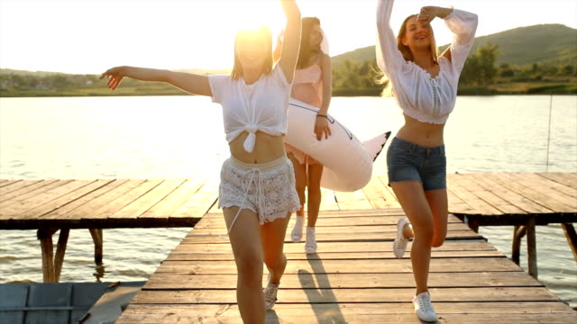 Carefree female friends having fun on lake with inflatable swan