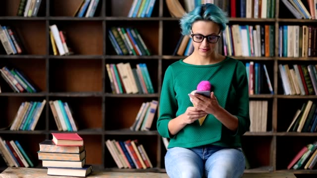 Carefree female student using phone in library Lovely hipster girl taking a break from studying and communicating with friends on social networks using smartphone in library. Happy female student texting feedback for internet forum on telephone while sitting on the bench near stack of books. blue hair stock videos & royalty-free footage