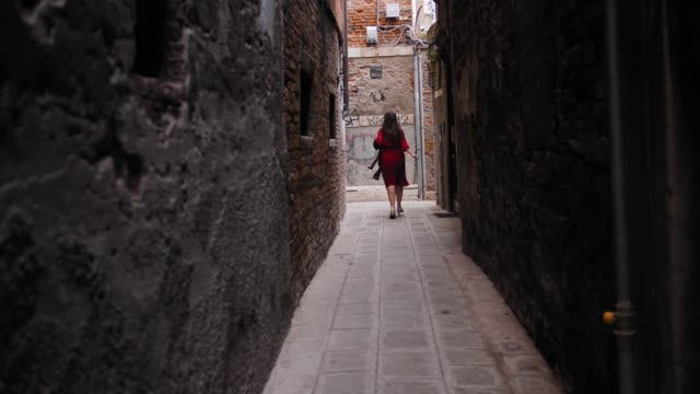 vídeos de stock e filmes b-roll de carefree female tourist with hat in hand running in the of venice yard - lago maggiore