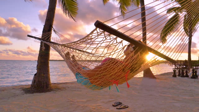 CLOSE UP: Carefree girl napping in a swaying hammock on golden summer evening. SLOW MOTION, LENS FLARE, CLOSE UP: Carefree girl napping in a swaying hammock on golden summer evening on the tranquil sandy beach in Cook Islands. Female tourist relaxing on the beach at sunrise. indian ocean stock videos & royalty-free footage