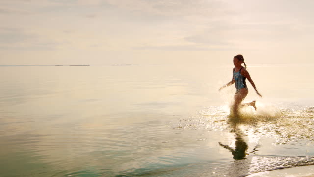 Carefree girl of 7 years running on the water. From her feet flying a lot of splashing video