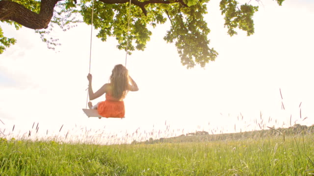 SLO MO Carefree girl on a tree swing video