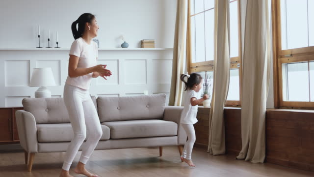 carefree healthy mom and child daughter having fun dancing together - two students together asian video stock e b–roll