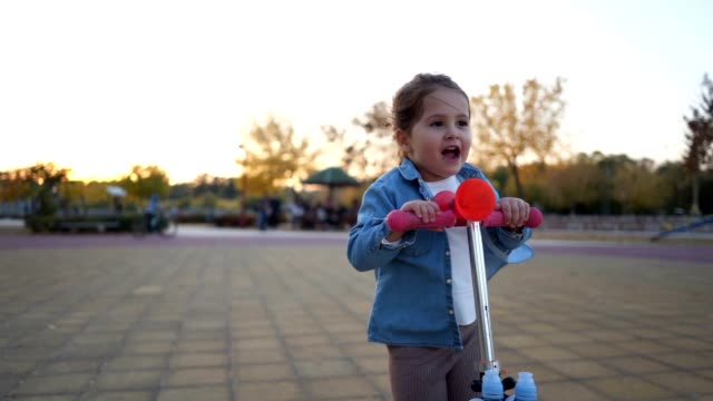 carefree little girl enjoys riding a toy push scooter - 2 3 anni video stock e b–roll