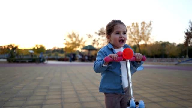 unbeschwertes mädchen genießt eine spielzeug-push motorroller - 2 3 jahre stock-videos und b-roll-filmmaterial