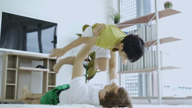 Carefree loving family adult dad hold cute little kid son pretend superhero plane having fun lying on the floor
