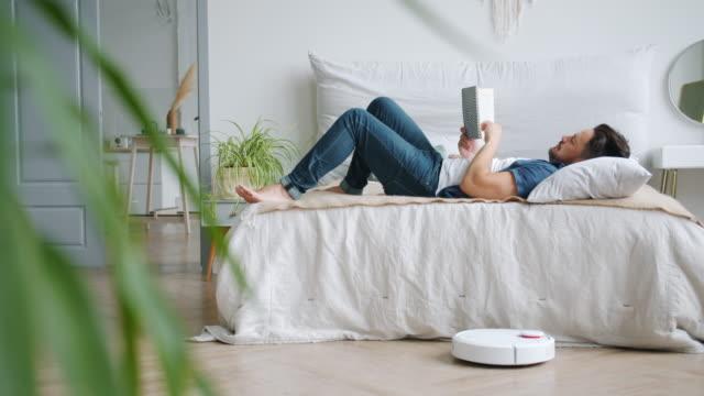 robotik elektrikli süpürge süpürge zemin vakumlama ise yatakta kaygısız adam kitap okuma - dinlenmek stok videoları ve detay görüntü çekimi