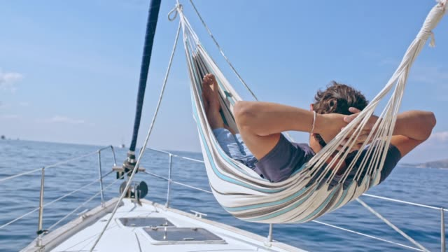 4k carefree man relaxing in hammock on sunny sailboat, real time - amaca video stock e b–roll