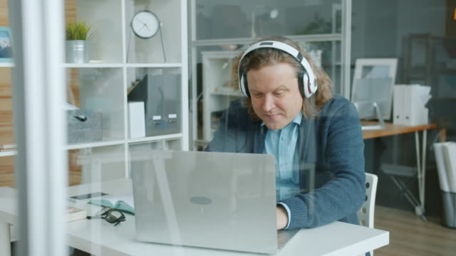 Carefree office worker working with laptop wearing headphones and dancing moving arms video