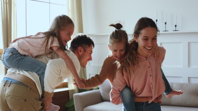 i genitori spensierati danno divertenti bambini carini giro in piggyback a casa - divertirsi video stock e b–roll