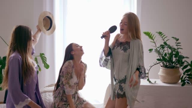 屈託のない残りの部分、女の子が部屋でシルクのバスローブでお友達と検討と踊りのようなヘアブラシに歌を歌う幸せ - ブラシ点の映像素材/bロール