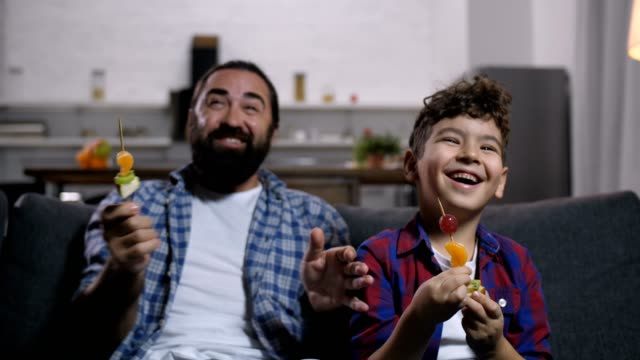 carefree smiling dad and son enjoying tv show - spiedino video stock e b–roll