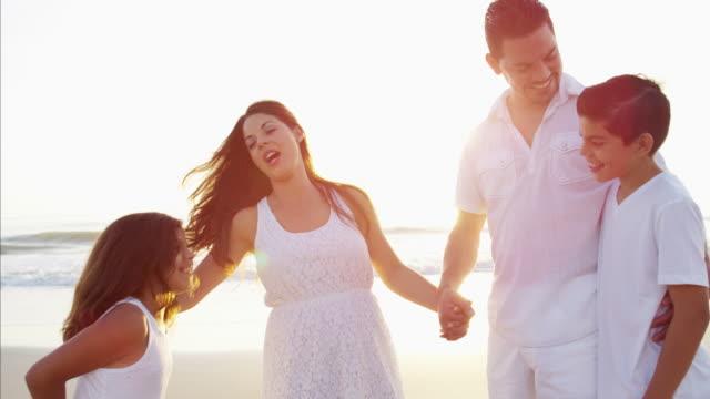 Carefree Spanish family having fun on the beach
