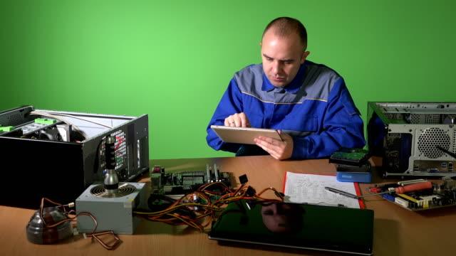 Carefree technician man using tablet talk with customer. broken computer parts