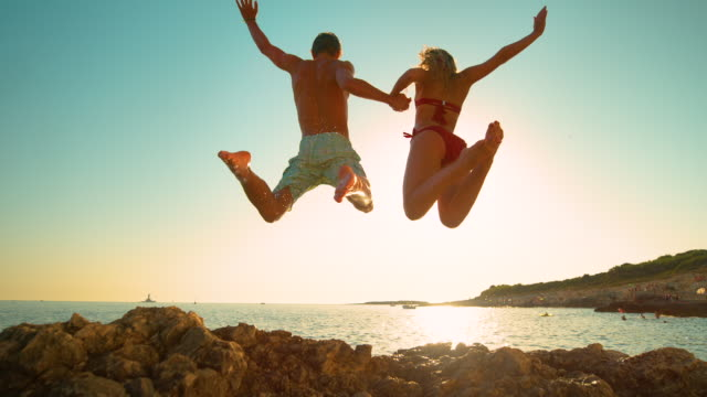 LENS FLARE: Carefree tourists hold hands while jumping into the refreshing sea SLOW MOTION, LOW ANGLE, LENS FLARE: Carefree tourists hold hands while jumping into the refreshing sea at sunset. Energetic couple holds hands while diving into the sea on a sunny summer evening. cliffs stock videos & royalty-free footage