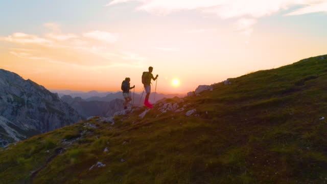 LENS FLARE: Carefree trekkers hiking uphill on a picturesque summer morning. video