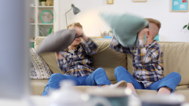 carefree twin boys having pillow fight on couch - gemelle video stock e b–roll