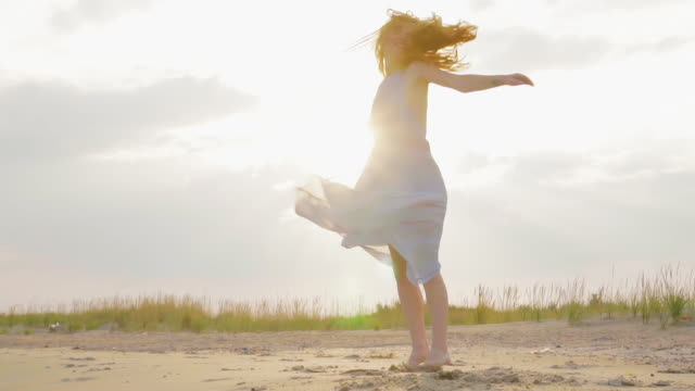 Carefree woman dancing on the sunset on the sea beach. Girl spinning. Femininity at sunset. Slow motion