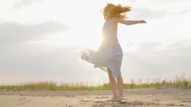 Zorgeloze vrouw dansen op de zonsondergang op het strand van de zee. Meisje spinnen. Vrouwelijkheid bij zonsondergang. Slow Motion video