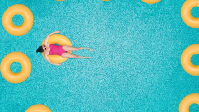 stockvideo's en b-roll-footage met zorgeloze vrouw op ring in zwembad - opblaasband