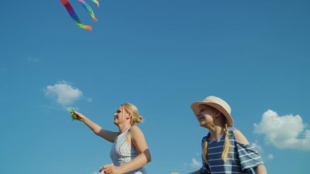 A carefree woman plays with her daughter, a girl tries to catch an air kite. Against the background of pure blue sky
