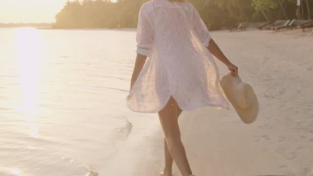 stockvideo's en b-roll-footage met ms carefree vrouw uitgevoerd en spetteren in zonnige ocean surf op witte zand strand bij zonsondergang, maldiven - mid volwassen vrouw