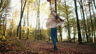 istock Carefree woman spinning and throwing dry leaves 1314595530